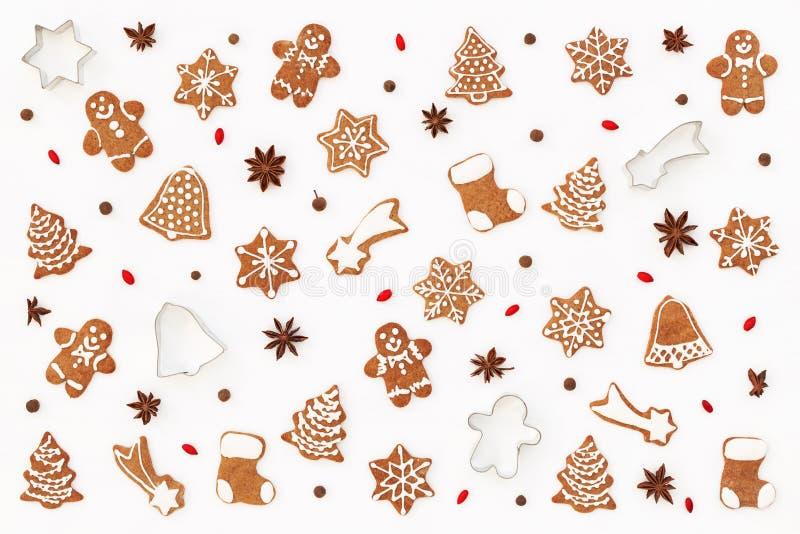 Teste padrão do Natal feito de cookies do pão-de-espécie, de anis de estrelas, de moldes de cozimento e de bérberis no fundo bran fotos de stock