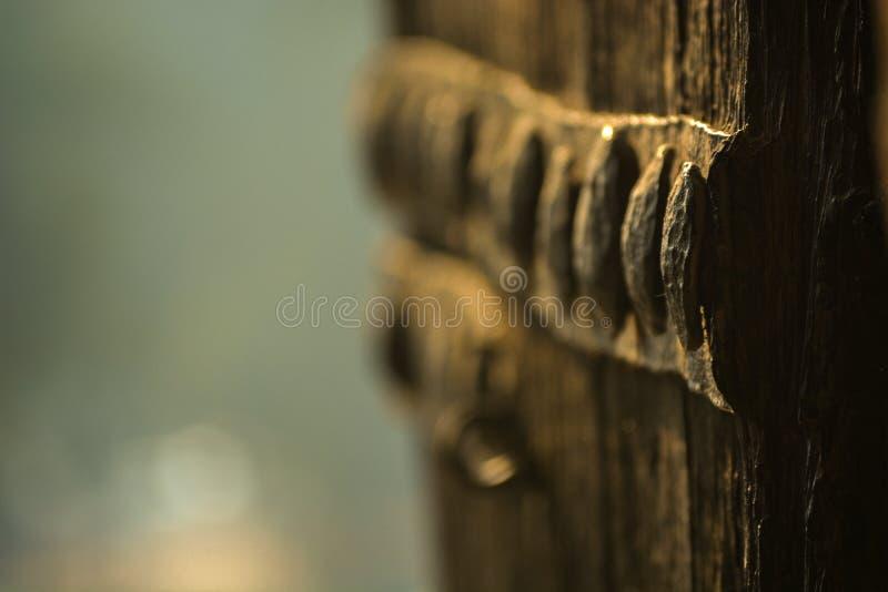 Teste padrão feito pelos parafusos metálicos em uma porta de madeira do forte velho situada em Nova Deli, Índia foto de stock