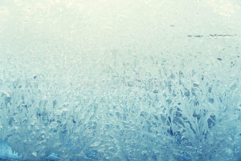 Teste padrão gelado no vidro, luz - azul imagem de stock