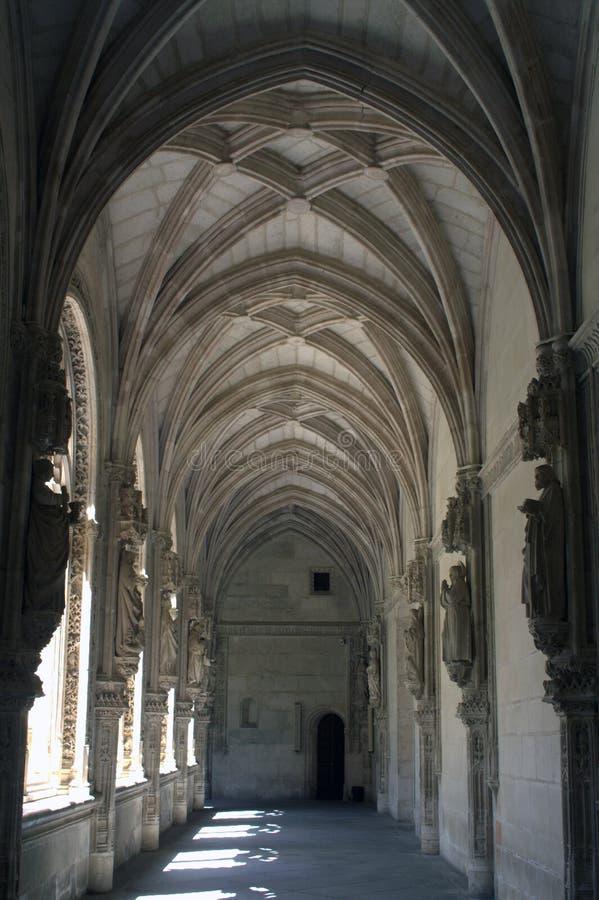 Teste padrão geométrico rítmico dos arcos e das sombras no corredor do monastério medieval foto de stock