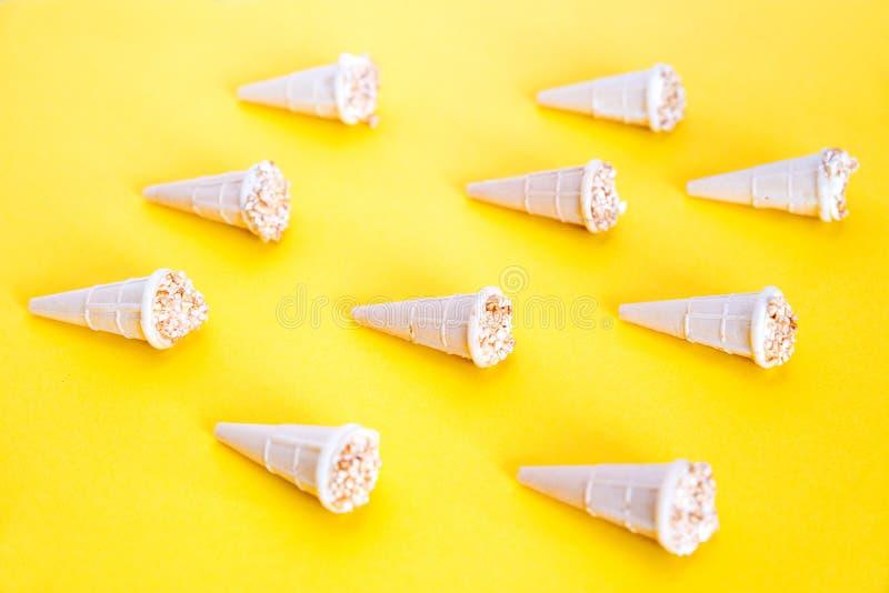 Teste padrão na moda do verão da luz solar Gelado com as porcas em uns copos do waffle Os cones do waffle apresentaram em um fund imagens de stock royalty free