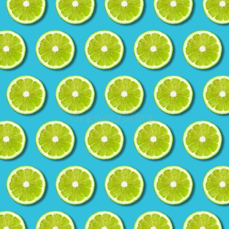 Teste padrão verde das fatias do cal no fundo vibrante de turquesa imagem de stock royalty free