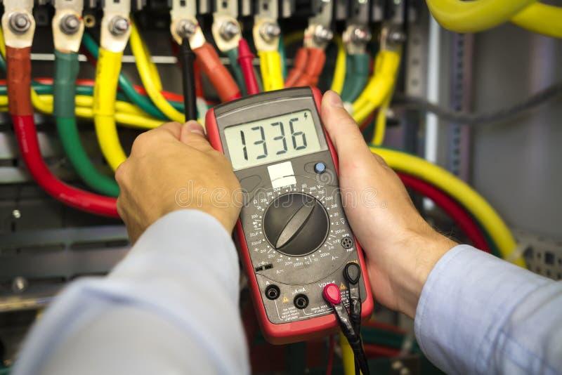 Tester elettrico in mani del primo piano dell'ingegnere Tecnico dell'elettricista sul lavoro che ispeziona il collegamento di cab fotografia stock
