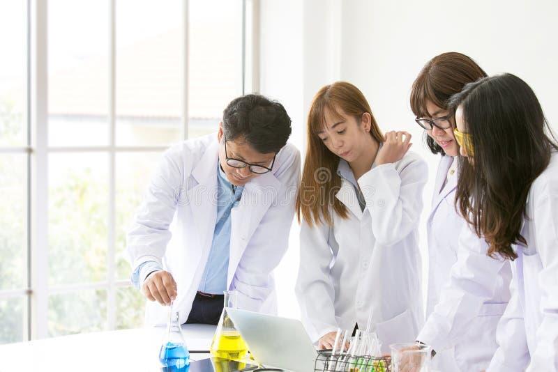 Testes científicos do químico do teste da ciência Cientista do grupo que trabalha no laboratório Uns homem e mulher três no labor foto de stock