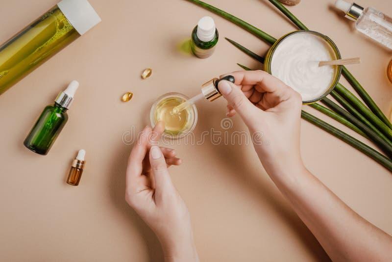 Testes dos cosméticos do cosmetologist da mulher Cosm?ticos org?nicos naturais Máscara do cabelo do soro Cor pastel colocada lisa foto de stock