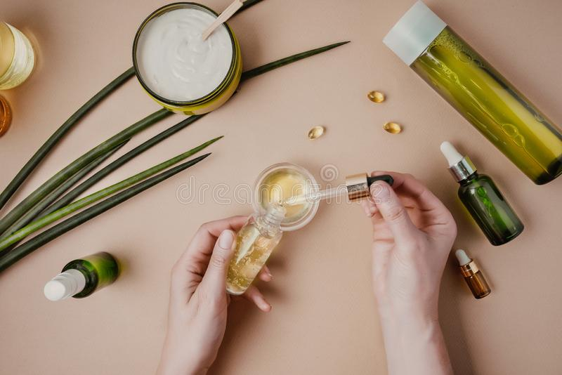 Testes dos cosméticos do cosmetologist da mulher Cosm?ticos org?nicos naturais Máscara do cabelo do soro Cor pastel colocada lisa imagens de stock