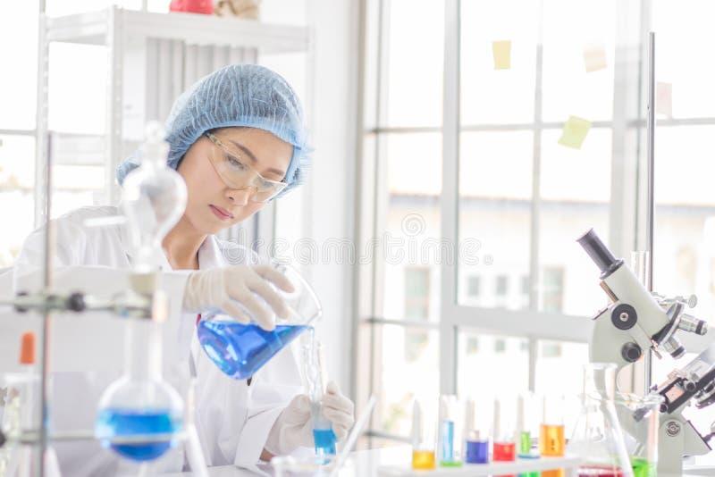Testes fêmeas do cientista sobre o produto químico no laboratório imagem de stock
