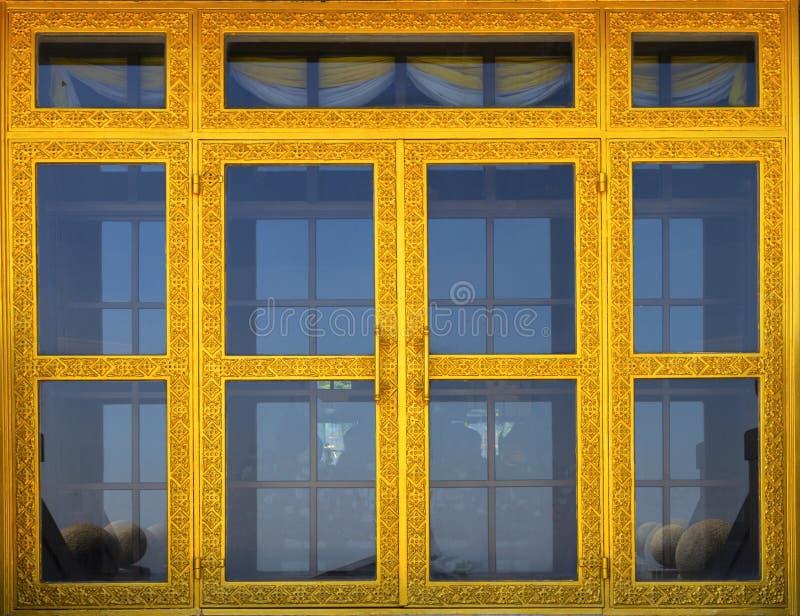 Testes padrões cinzelados em portas de madeira do ouro no templo tailandês fotos de stock
