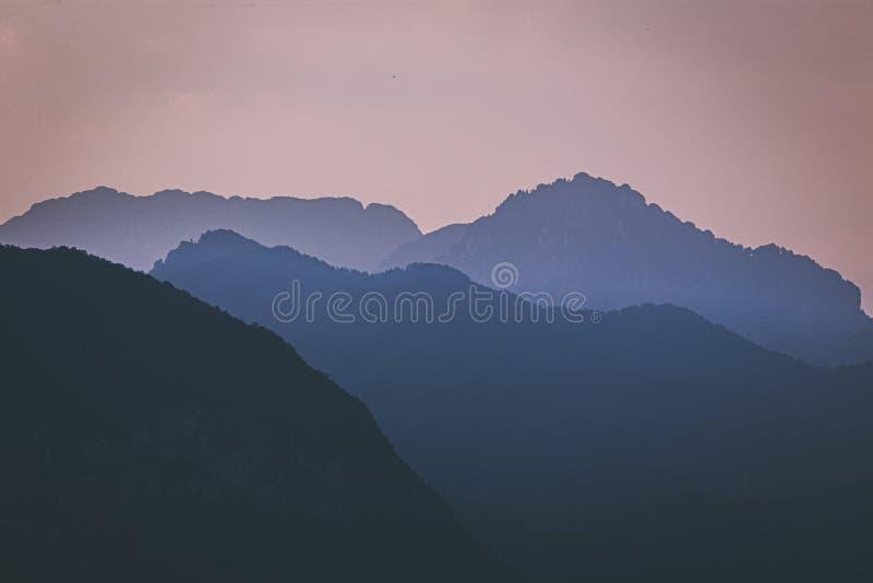 Testes padrões naturais: camadas de montanhas em uma luz suave nevoenta no por do sol Lago Garda, Italy Artístico, quase abstrato imagens de stock