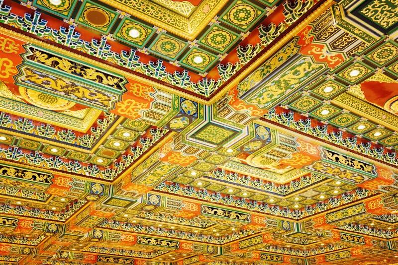 Testes padrões vermelhos dourados no teto no interior do Po Lin Mon fotografia de stock royalty free