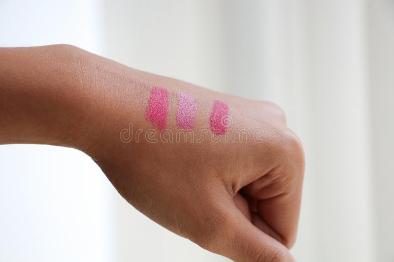 Testing color shades Lipstick on Asian female hand cosmetics ma. Ke-up bright pink color style for choosing beautiful one royalty free stock image