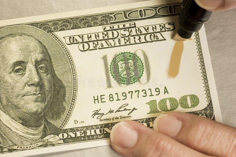 Testing Counterfeit Money royalty free stock photo