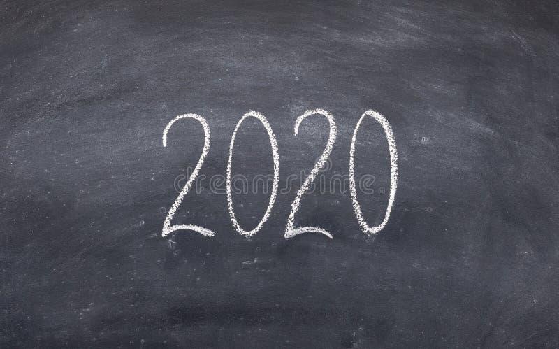 Testo bianco 2020 della scrittura sul bordo del ckalk con lo spazio della copia fotografia stock libera da diritti
