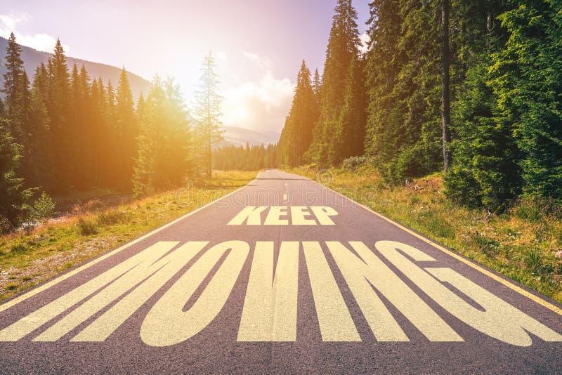 Testo commovente Keep scritto sulla strada nelle montagne immagini stock