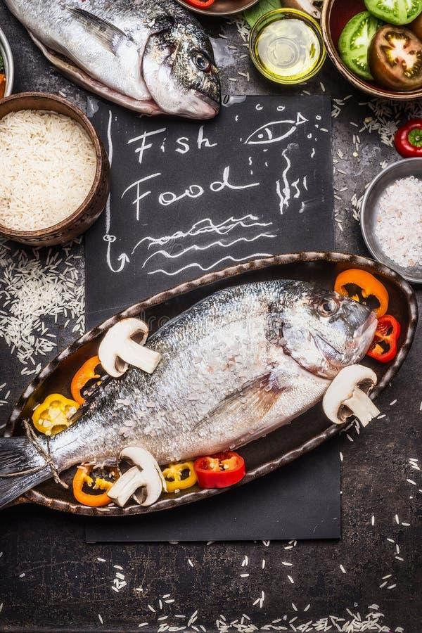 Testo del mangime per pesci con il dorado, il riso crudo e le verdure cucinanti gli ingredienti su fondo rustico scuro, vista sup fotografia stock libera da diritti