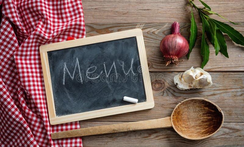 Testo del menu su una lavagna, sulle erbe e su una siviera sulla tovaglia rossa e sulla tavola di legno, vista superiore immagine stock libera da diritti
