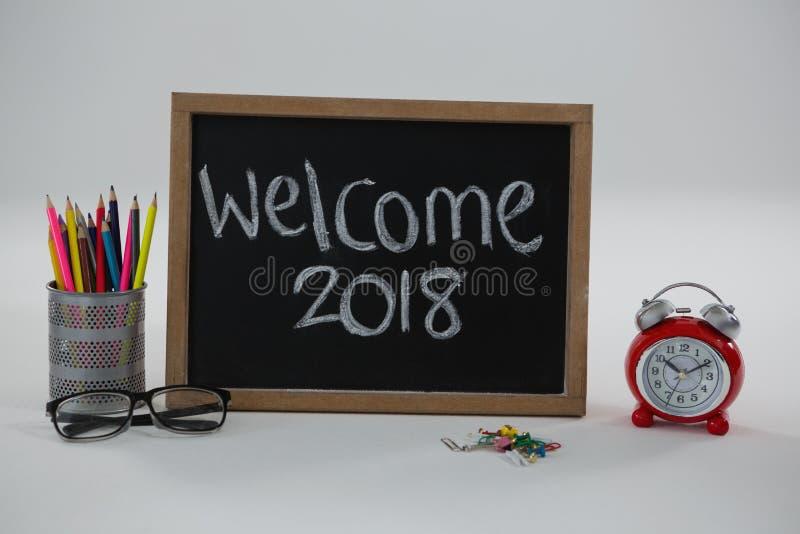 Testo di benvenuto 2018 sulla lavagna con i vari rifornimenti di scuola fotografia stock