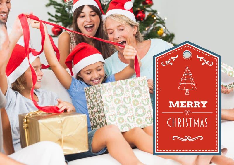 Testo di Buon Natale con i presente di apertura della famiglia fotografia stock