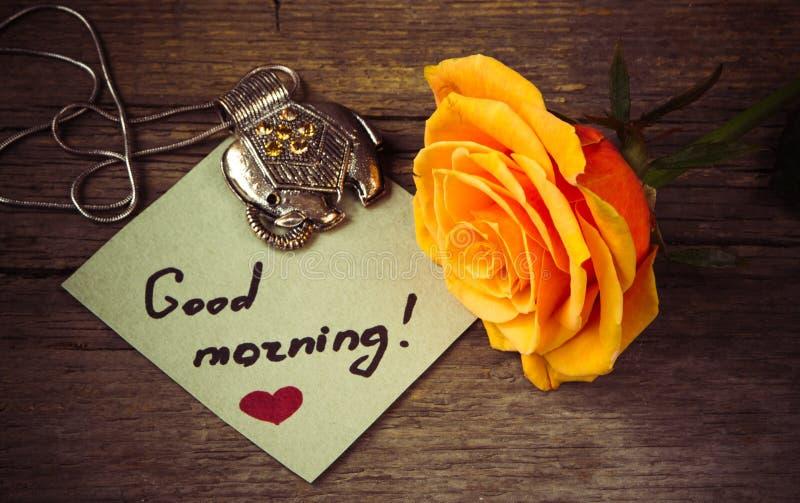 Testo di buongiorno su una carta, su un fiore dell'arancia e su una decorazione rosa fotografia stock