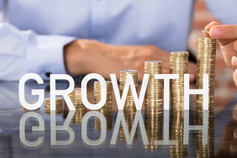Testo di crescita in Front Of Coins Stack immagine stock