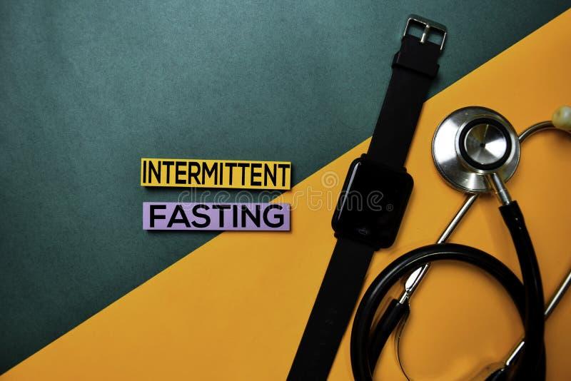 Testo di digiuno intermittente sulla tavola di colore di vista superiore e sulla sanità/concetto medico fotografie stock