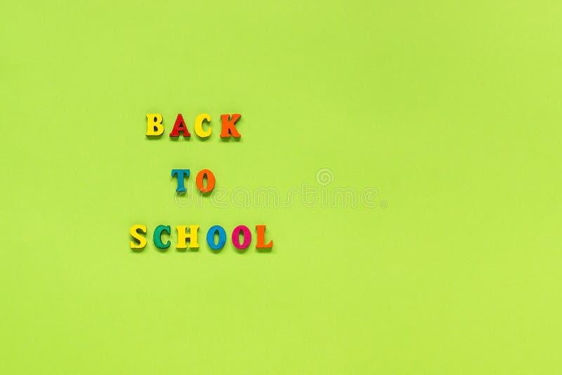 Testo di nuovo a scuola dalle multi lettere colorate sul modello dello spazio della copia di vista superiore di istruzione di con fotografie stock
