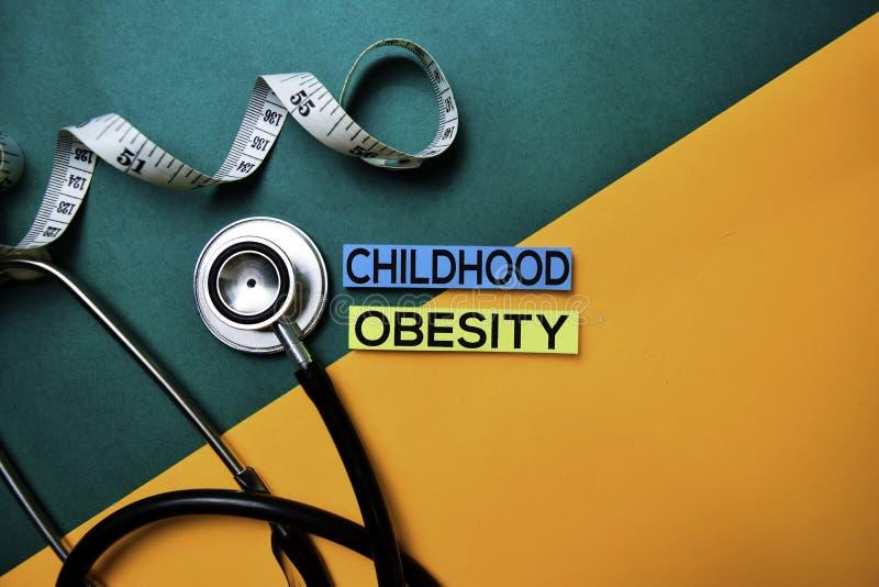Testo di obesità di infanzia sulla tavola di colore di vista superiore e sulla sanità/concetto medico immagine stock