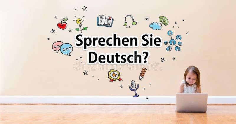 Testo di Sprechen Sie Deutsch con la bambina che per mezzo di un computer portatile fotografia stock libera da diritti