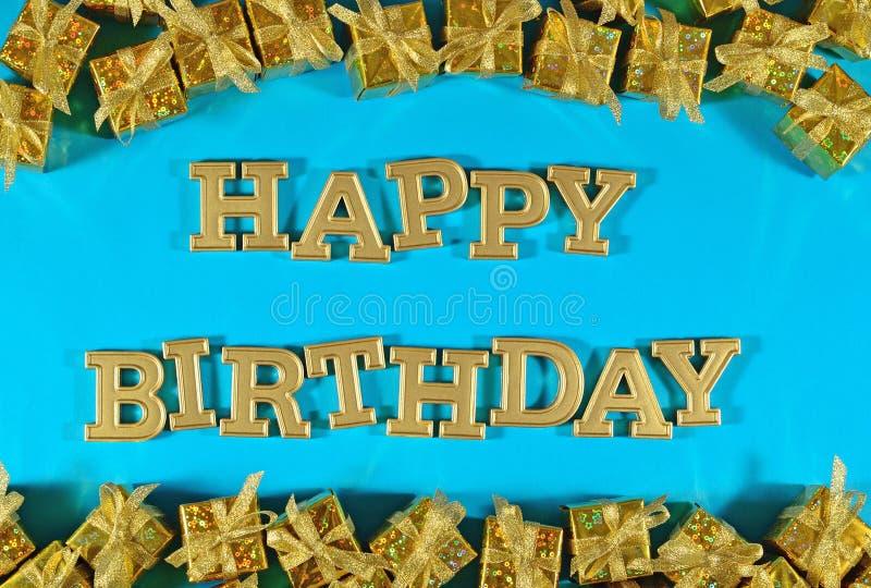 Testo dorato di buon compleanno e regali dorati su un blu immagine stock