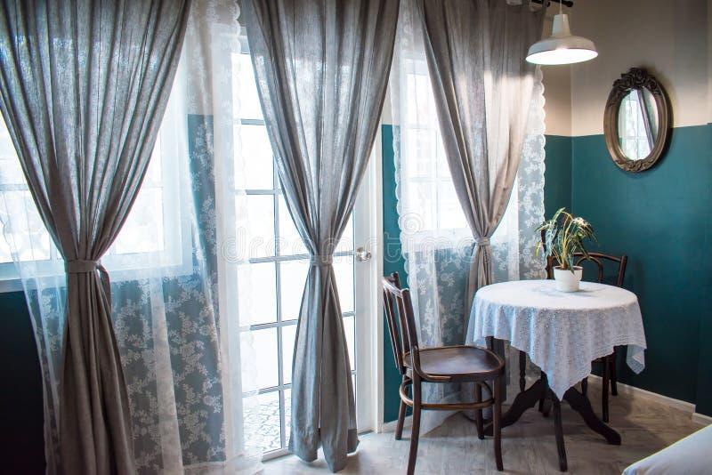 Tetabellen ställde in med växtkrukor bredvid stora fönster och stora gråa gardiner med solljusfiltret arkivfoton
