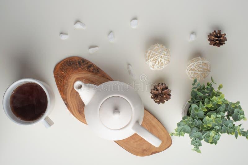 Tetera blanca de cerámica con los accesorios en una tabla blanca, marco horizontal, tiempo del té, té que bebe, fabricación retua imagen de archivo