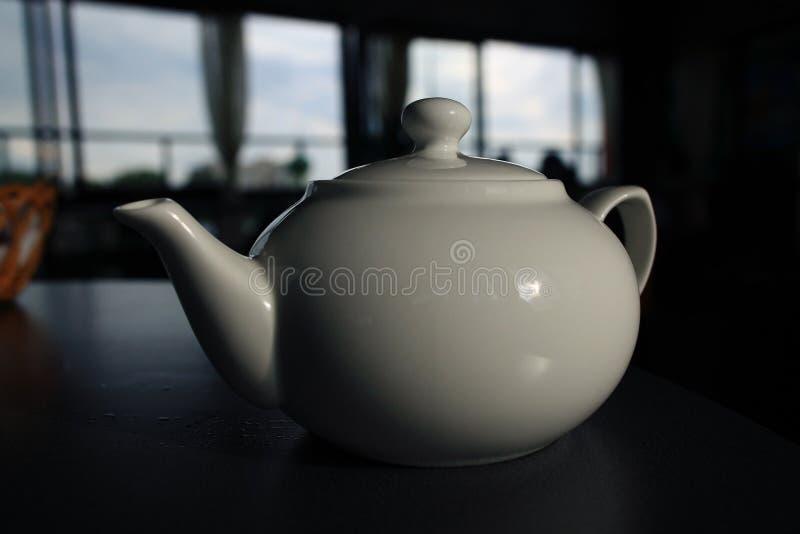 Tetera blanca en café imagen de archivo