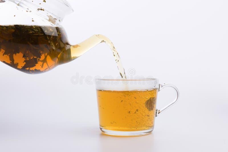 Tetera de cristal que vierte té verde en la taza aislada en el fondo blanco fotos de archivo