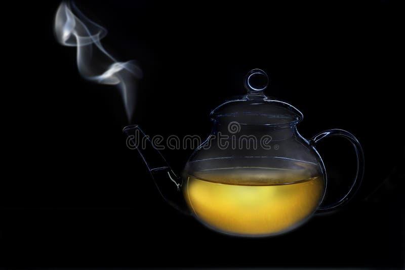 Tetera de cristal transparente con humo del canalón imagenes de archivo