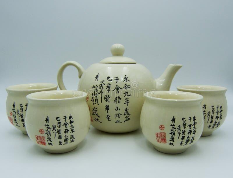 Tetera de Oriental, una taza, fondo blanco imagen de archivo
