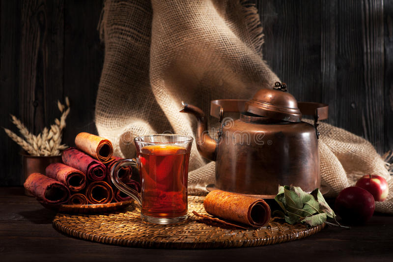 Tetera del vintage con té, dulces y manzanas fotos de archivo