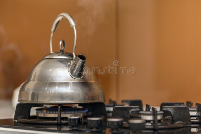 Tetera inoxidable brillante de la caldera de té con el agua hirvienda en estufa de gas en fondo amarillo del espacio de la copia  imagen de archivo