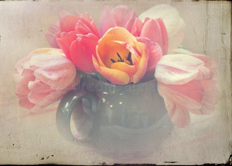 Tetera verde apenada de tulipanes bonitos imagen de archivo