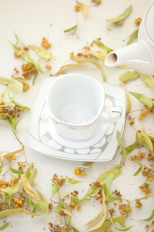 Tetera y taza con t? y flores del tilo fotografía de archivo libre de regalías