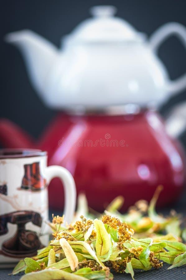 Tetera y taza con t? y flores del tilo fotografía de archivo