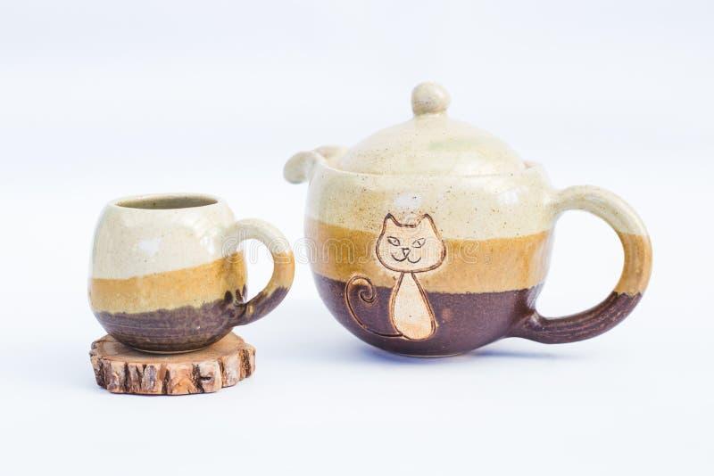 tetera y taza de cerámica del gres con el fondo blanco foto de archivo libre de regalías