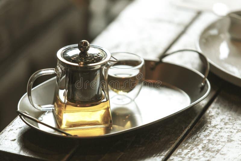 Tetera y taza de cristal transparentes de té en la bandeja de acero inoxidable fotos de archivo