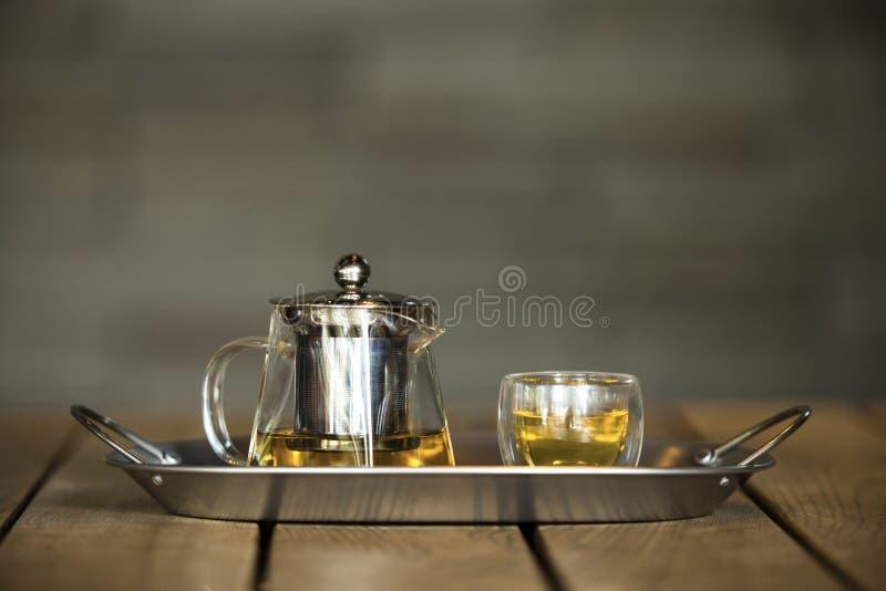 Tetera y taza de cristal transparentes de té en la bandeja de acero inoxidable fotografía de archivo