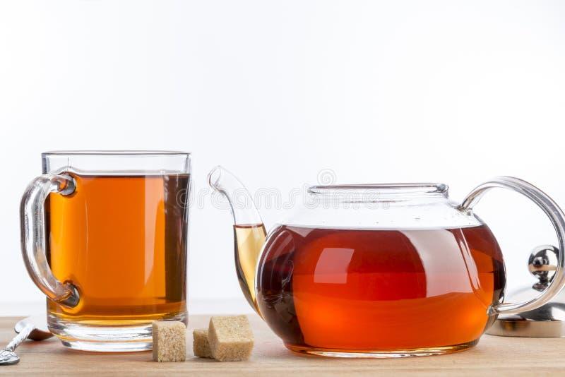 Tetera y taza de té en el fondo de madera de la tabla imagen de archivo