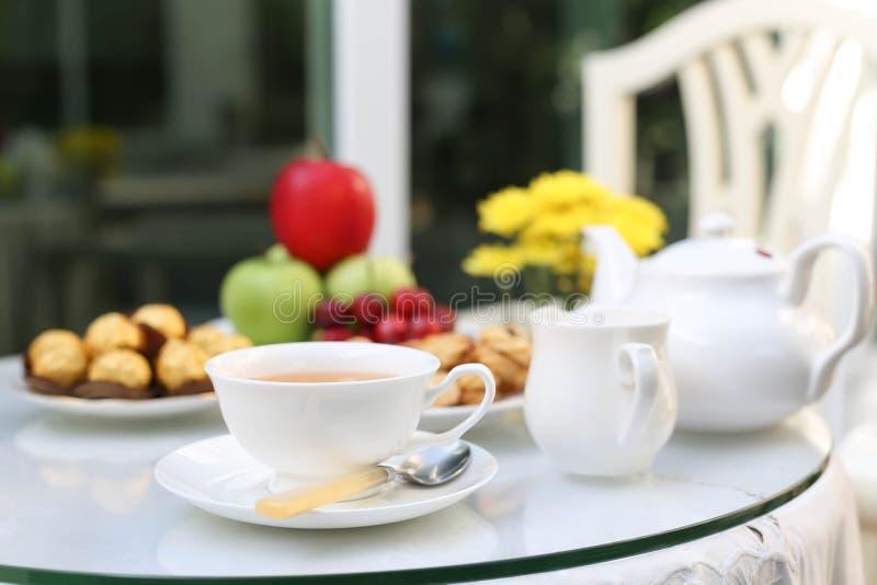 Tetid med choklad och kakor eller kex och frukt royaltyfria foton