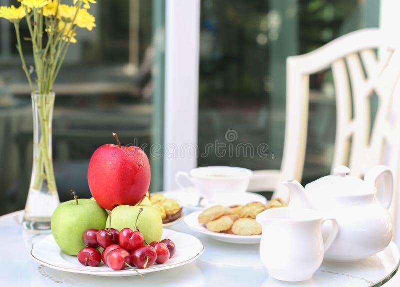 Tetid med choklad och kakor eller kex och frukt arkivfoton