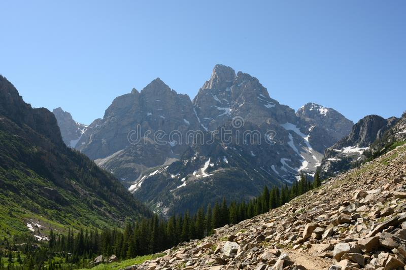 Tetons Loom Over Pine Trees and Boulder Field royalty free stock photo