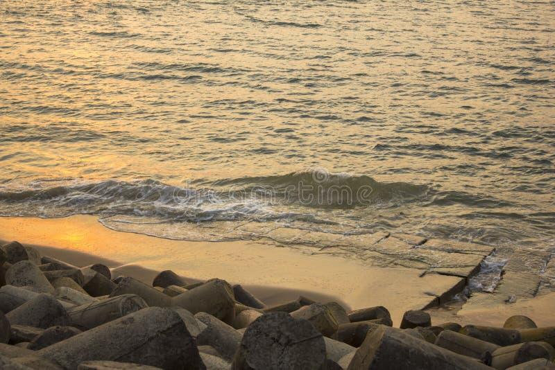Tetrapods borrados no fundo de uma terraplenagem concreta e do mar Barreira do tsunami imagens de stock royalty free