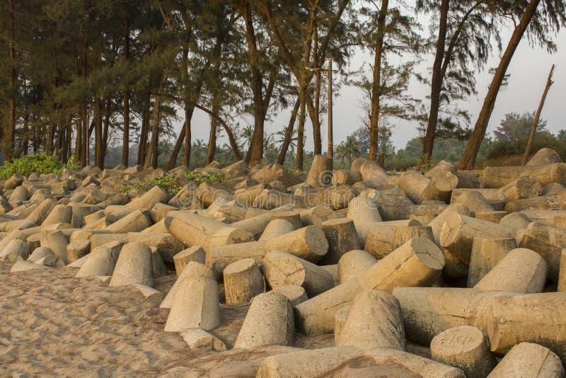 Tetrapods concretos em um Sandy Beach no fundo das árvores e das palmas Barreira do tsunami imagens de stock royalty free
