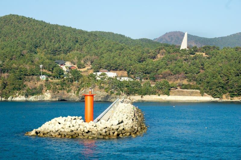 Tetrapodsgolfbreker met rood die baken in DSME-baai met de mening van Admiraals yi Sun-Zonde monument in Okpo wordt gevestigd royalty-vrije stock foto